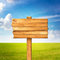Stock Image : Wooden sign over beautiful green meadow and blue sky