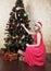 Stock Image : Young beautiful girl in Santa hat near Christmas tree