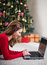 Stock Image : Young woman using a laptop in front of Christmas tree