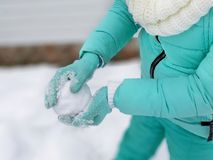Snowball on female hands in seal knitted mittens. stock image