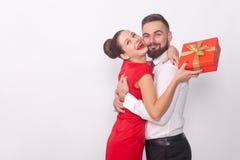 ¡Él presente del ` s para usted! Pares que abrazan, mujer que sostiene la caja de regalo foto de archivo libre de regalías