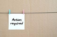 ¡Acción requerida! La nota se escribe en una etiqueta engomada blanca que cuelgue w Foto de archivo