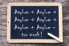 ¡Asilo + asilo + asilo = demasiado! Demasiado asilo escrito en una pizarra Imágenes de archivo libres de regalías