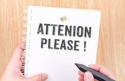 ¡Atención por favor! palabra en el cuaderno blanco de la carpeta de anillo con la mano h Fotos de archivo