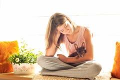 ¡Buenos días! Chica joven en los pijamas que sostienen su perro precioso Imágenes de archivo libres de regalías