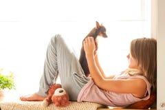 ¡Buenos días! Chica joven en los pijamas que sostienen su perro precioso Foto de archivo