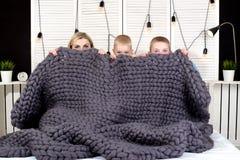 ¡Buenos días! La madre y dos pequeños hijos ocultan debajo de una manta hecha punto El despertar positivo foto de archivo libre de regalías