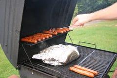 ¡Cocinar los perritos calientes en la parrilla 2! imagen de archivo