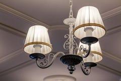 ¡De Ð más handelier con tres lámparas eléctricas y pantallas que cuelgan encendido foto de archivo