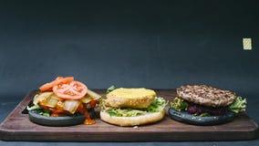 ¡De Ð ooking dos hamburguesas negras y un cheeseburger en un fondo negro en time lapse de la resolución 4k metrajes