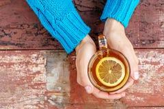 ¡De Ð para arriba del té caliente con el limón Manos Concepto de bebidas, forma de vida a Imágenes de archivo libres de regalías