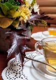 ¡De Ð para arriba del té y de las flores en la tabla fotografía de archivo