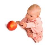 ¡El bebé quiere conseguir la manzana! Imagen de archivo