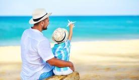 ¡El día de padre feliz! hijo del papá y del niño en la playa por el mar con el avión modelo del juguete imagen de archivo libre de regalías