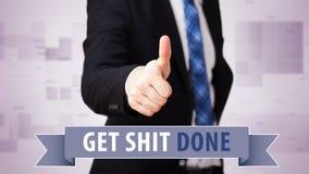 ¡El pulgar de las demostraciones del hombre de negocios hasta ` consigue mierda hecha! ` foto de archivo