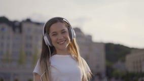 ¡Estoy feliz y libre! muchacha divertida que camina en la ciudad, madrugada mujer en los auriculares grandes que bailan y que can almacen de video