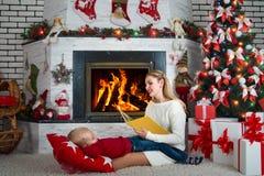 ¡Feliz Navidad! La mamá está leyendo un libro a un pequeño hijo con cuentos de hadas La familia está descansando cerca de la chim Fotografía de archivo libre de regalías