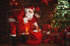 ¡Feliz Navidad! Papá Noel cerca de la chimenea y del árbol con el regalo Imagen de archivo