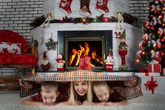 ¡Feliz Navidad! Una madre joven y dos hijos cubiertos con la tela escocesa, mentira en la alfombra cerca de la chimenea La famili Imágenes de archivo libres de regalías