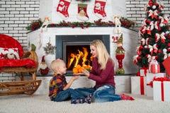 ¡Feliz Navidad y buenas fiestas! La mamá y el hijo que juegan cerca de la chimenea, comen las mandarinas Foto de archivo