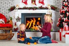 ¡Feliz Navidad y buenas fiestas! La mamá y el hijo que juegan cerca de la chimenea, comen las mandarinas Imagen de archivo libre de regalías