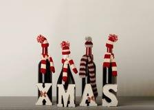 ¡Feliz Navidad y una Feliz Año Nuevo! Botellas de vino en un knitt Imagen de archivo