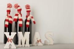 ¡Feliz Navidad y una Feliz Año Nuevo! Botellas de vino en un knitt Fotos de archivo