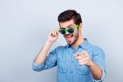 ¡Fresco! El hombre joven hermoso juguetón en vidrios verdes claros es poin Fotografía de archivo libre de regalías