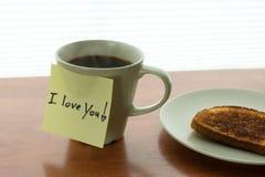 ¡Gesto romántico te amo! nota sobre la taza de café caliente en luz de la mañana Imágenes de archivo libres de regalías