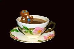 ¡Goce de esta tina caliente! Hombre de pan de jengibre en taza de chocolate caliente Imagen de archivo