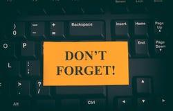 ¡La nota de papel amarilla sobre el teclado negro con la escritura del ` t de Don olvida! Fotografía de archivo