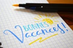 ¡Lengua francesa BONNES VACANCES! mano-indicado con letras en cuaderno Foto de archivo libre de regalías