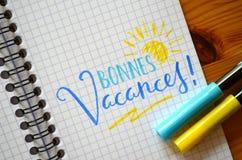¡Lengua francesa BONNES VACANCES! mano-indicado con letras en cuaderno Foto de archivo