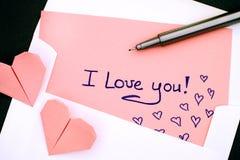 ¡Letra con el texto te amo! en sobre con dos papiroflexia rosada h Imagen de archivo libre de regalías