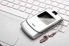 ¡Llámeme! Teléfono móvil en una computadora portátil blanca. Imágenes de archivo libres de regalías