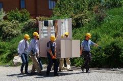 ¡Los trabajadores transportan el marco de los muebles a las cáscaras públicas! Fotografía de archivo libre de regalías