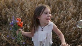 ¡Niña en un campo de trigo en la puesta del sol con un ramo de flores salvajes! metrajes