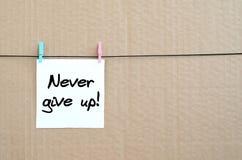 ¡Nunca abandone! La nota se escribe en una etiqueta engomada blanca que cuelgue ingenio Imagen de archivo libre de regalías