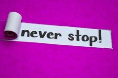 ¡Nunca parada! texto, concepto de la inspiración, de la motivación y del negocio en el papel rasgado púrpura imagenes de archivo