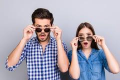 ¡Oh realmente?! ¡Guau! Sorprenden a dos amantes chocados los jóvenes con los ojos abiertos de par en par, mouthes, vidrios de sol fotografía de archivo libre de regalías