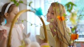 ¡Pascua feliz! La madre y la hija que se divierten y se pintan las caras de los conejitos del ` s metrajes