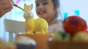 ¡Pascua feliz! Mime y su pequeña hija con los oídos del conejito que pintan el conejito de pascua almacen de metraje de vídeo