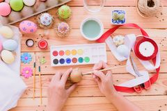 ¡Pascua feliz! Una mano de la mujer que pinta los huevos de Pascua imagenes de archivo
