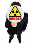 ¡Peligro de la radiación! Hombre de negocios con la muestra de la radiación Foto de archivo libre de regalías