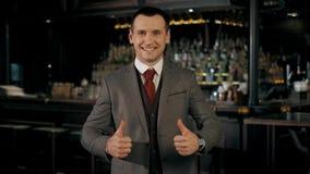 ¡Pozo hecho! El hombre de negocios feliz acertado está mostrando el pulgar para arriba Él es hermoso, sonriendo, su compañía alca metrajes