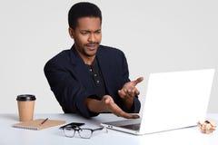 ¡Qué absurdo! Puzzled descontentó descontento afroamericano negro del hombre con las figuras financieras en proyecto del negocio, foto de archivo libre de regalías