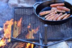 ¡Salchichas del desayuno que cocinan en una hoguera! Foto de archivo