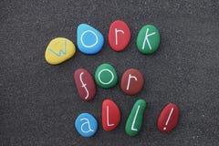 ¡Trabajo para todos! Lema social con las piedras multicoloras sobre la arena volcánica negra Imagen de archivo