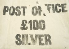 £100 silver printed on a vintage Post Office bank money bag. £100 / one pounds silver printed on a vintage Post Office bank deposit cash / cloth money bag Royalty Free Stock Photo