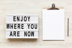 «Cieszy się dokąd ty jesteś teraz «słowami na lightbox, noticeboard, ołówek zdjęcia stock